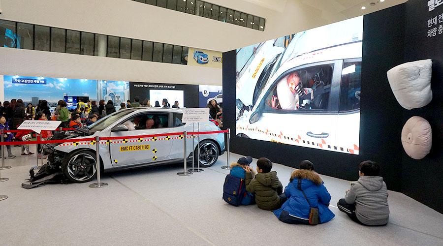 충돌 테스트 차량 및 에어백 전시 구경하는 어린이들 사진